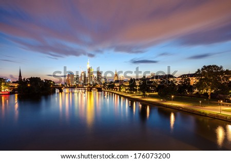 Frankfurt city skyline after sunset with colorful clouds over the river - stock photo
