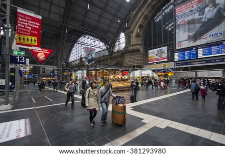Frankfurt, Germany - April 30, 2014: Asian couple with suitcase and other train travelers walk among the kiosks in the central hall of Frankfurt railway station in Frankfurt, Germay on April 30, 2014 - stock photo