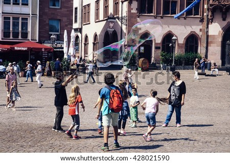 FRANKFURT, GERMANY- AUGUST 22, 2015 : Tourists enjoying the buildings of the historical landmark of Romerberg square and children having fun with water baloons  - stock photo