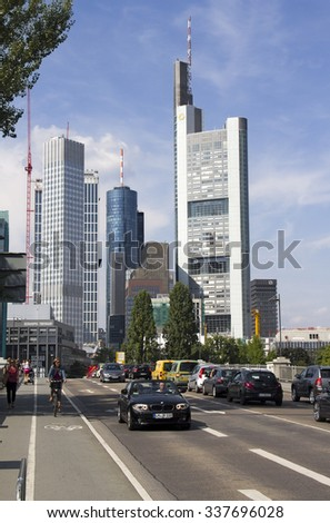 Frankfurt, Germany - August 29, 2013: Traffic of cars and a cyclist drive on a bridge across the Main river with tall office buildings in the background in Frankfurt, Germany on August 29, 2013.
