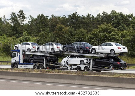 FRANKFURT, GERMANY - JULY 12, 2016: Car tranporter truck with new Mercedes Benz automobiles on the highway in Germany