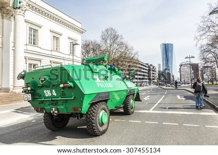 FRANKFURT, GERMANY - MAR 18, 2015: police is equiped with water guns against people demonstrate at EZB  in Frankfurt, Germany. 30 tsd. people join the demo. - stock photo