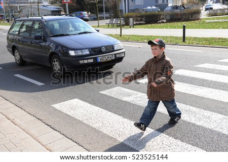 Frankfurt, Germany- March 20, 2009 - Children crossing street with guiding help of german officer