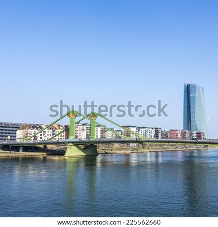 FRANKFURT, GERMANY - MARCH 3, 2014: View of the city with Floessserbruecke  with river Main in Frankfurt, Germany. The Floesser bridge was inaugurated in 1984 and has a length of 221 meter.