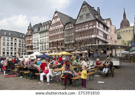 Frankfurt, Germany - May 1, 2014: People sit at long tables during the May 1 Labor Day celebration on the historical Marktplatz townsquare of Frankfurt, Germany on May 1, 2014