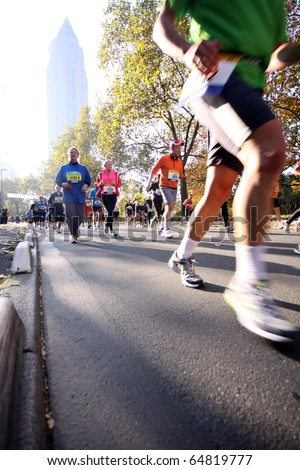 FRANKFURT, GERMANY - OCT 31: Unidentified runners in the Frankfurt Marathon on October 31, 2010 in Frankfurt, Germany. The race, currently sponsored by Commerzbank, is Germany's oldest city marathon. - stock photo