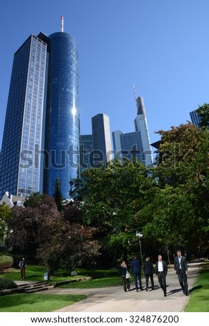 Frankfurt, Germany - October 1, 2015 - Main Tower and Commerzbank Tower seen from Taunusanlage with banker walking by during their lunch break