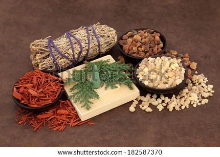 Frankincense, myrrh, sandalwood, incense cones , cedar leaf and smudge stick over lokta paper background. - stock photo
