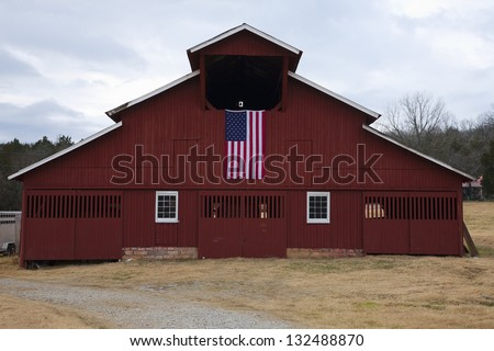 FRANKLIN, TN - DECEMBER 01: Red Barn and US Flag outside of Franklin a suburb south of Nashville on December 01, 2012 in Williamson County, Tennessee - stock photo
