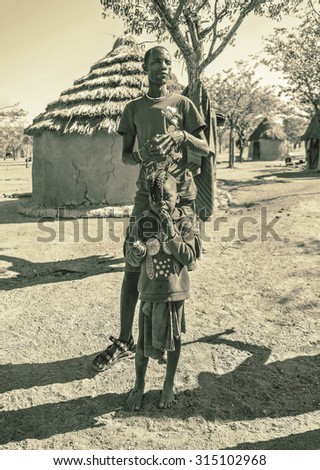 FRANSFONTEIN, NAMIBIA - JULY 09, 2014: A man Himba tribe with the child. The Himba are indigenous peoples living in northern Namibia, in the Kunene region of South-West Africa (stylized retro)