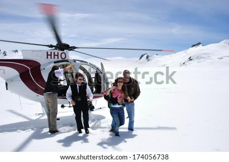 FRANZ JOSEF GLACIER, NEW ZEALAND: DECEMBER 24, 2009: Unidentified passengers alight from a helicopteter onto the snow above Franz Josef Glacier, Westland, New Zealand - stock photo