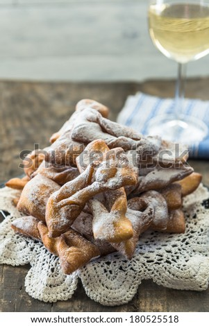 Frappe - typical Italian carnival fritters dusted with icing sugar with a glass of white wine in the background  - stock photo