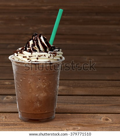 Frappuccino in takeaway cup on wooden table - stock photo