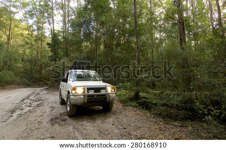 FRASER ISLAND, AUSTRALIA - JUNE 2007 : A white SUV in the tropical forest of Fraser island, the largest sand island of the world off the coast of Queensland Australia. - stock photo