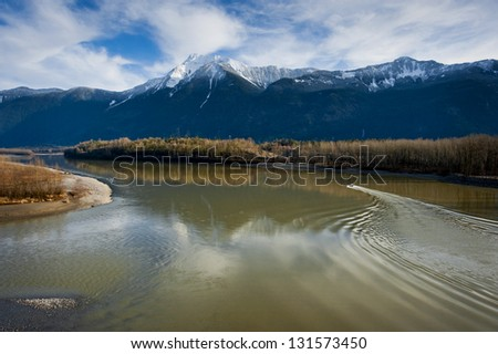 Fraser River, British Columbia, A small boat heads up the beautiful Fraser River surrounded by snow capped mountains in the western region of British Columbia. - stock photo