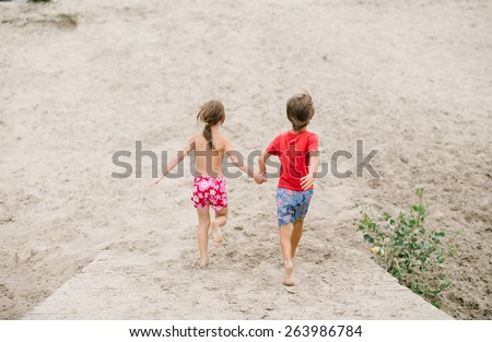 Fraternal twins run barefoot holding hands at the beach. Active healthy kids enjoying their time at the beach. Brother and sister playing together. Friends having fun during summer vacation.  - stock photo