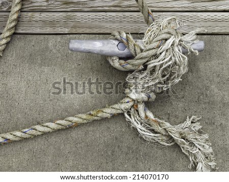Frazzled line holding a boat to a cleat on dock in marina - stock photo