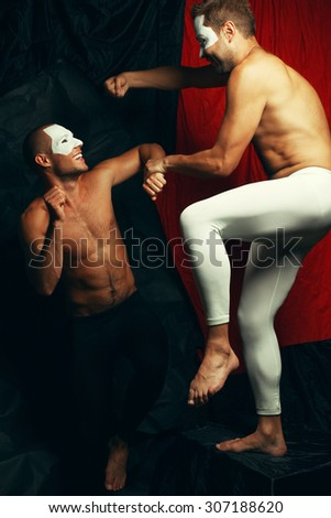 Freak circus concept. Two muscular mime artists, clowns with white masks on faces playing fools and fighting over red cloth & black background. Vintage style. Studio shot - stock photo