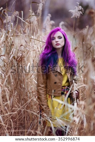 Freak girl with purple hair in high autumn grass