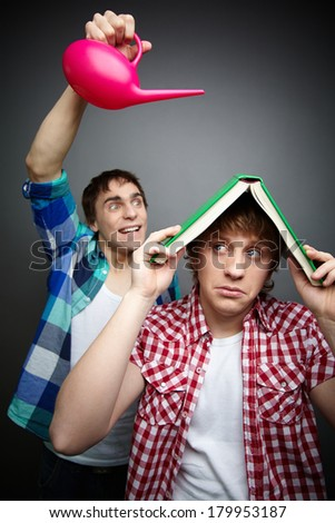 Freaky guy pouring water over his friend hiding under a book, fool�¢??s day celebration
