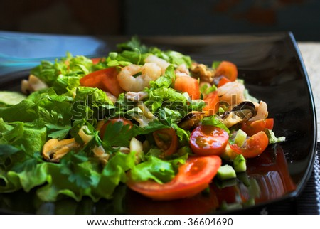 Freash vegetables salad with shrimps on the black dish.