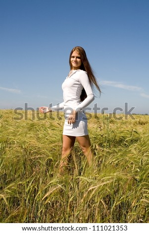 Freckled girl in a field with spikelets