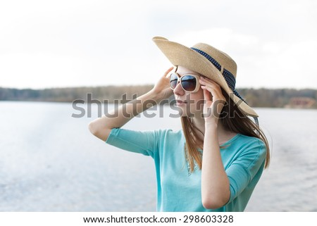 Freckled girl in hat looking through glasses of the lake