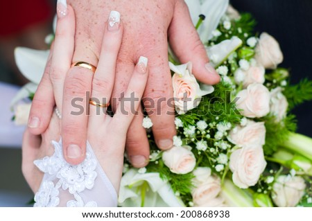 Freckled hands of bride and groom clasped together showing wedding rings - stock photo