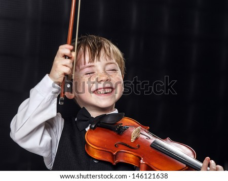 Freckled red-hair boy playing violin. Young musician. - stock photo