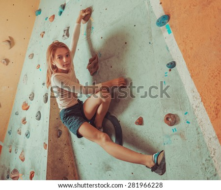 Free climber little girl climbing on artificial boulders in gym, looking at camera - stock photo