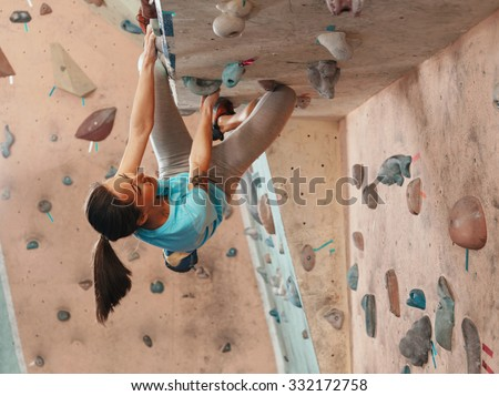 Free climber young woman climbing on a rock wall indoor, bouldering