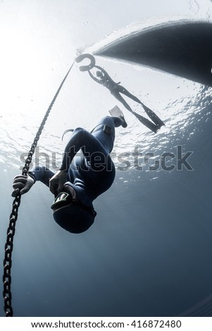 Free diver descending along the metal chain - stock photo