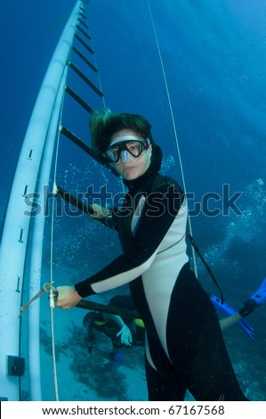 free diver poses on underwater wreck - stock photo