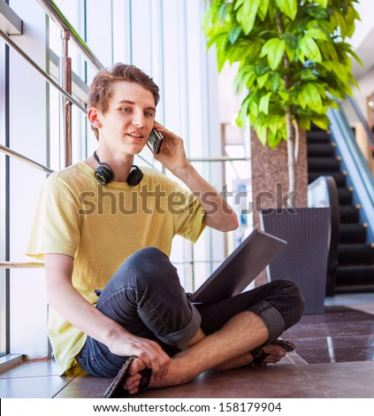 Free feeling teenage boy talking by phone sitting on the floor in commercial center - stock photo
