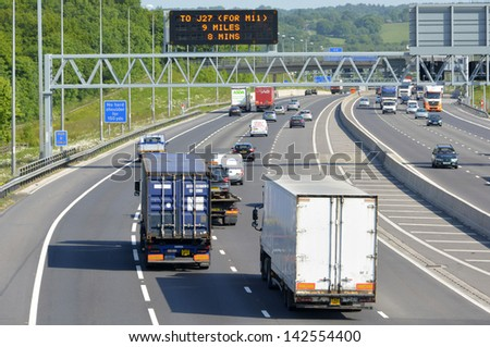 Free flowing traffic on  rural section of four lane dual carriageway M25 motorway in Essex England with active electronic overhead information sign - stock photo