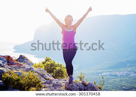 free happy caucasian female standing on the top of mountain with cheering hands. active and healthy woman hiking in mountains in crimea - stock photo