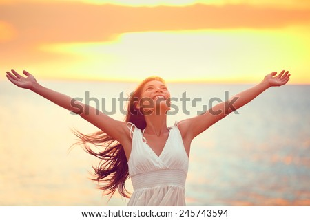 Free happy woman arms up praising freedom at beach sunset. Young adult enjoying breathing freely fresh air. - stock photo