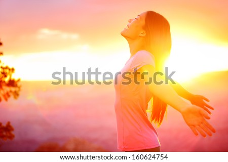 Free happy woman enjoying nature sunset. Freedom, happiness and enjoyment concept of beautiful multiracial Asian Caucasian girl in her 20s. Image from Grand Canyon, United States. - stock photo