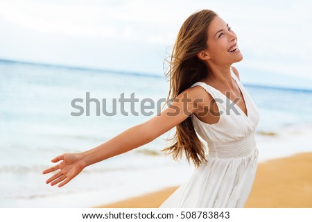 Free happy woman on beach enjoying nature. Natural beauty girl outdoor in freedom enjoyment concept. Mixed race Caucasian Asian girl posing on travel vacation holidays in dress.
