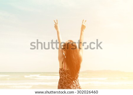 free happy woman open arms and with hands of fight sign at sunset - stock photo