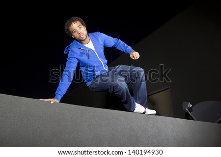 free runner doing parkour at night on a rooftop - stock photo