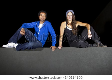 free runner scaling or climbing a wall at night to do parkour - stock photo