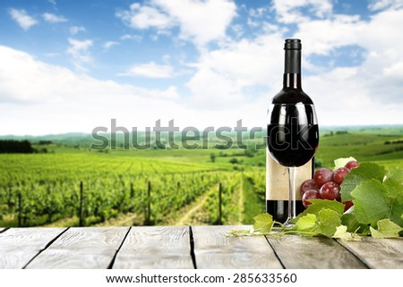 free space on wooden old table with wine and bottle and fresh fruits with leaves
