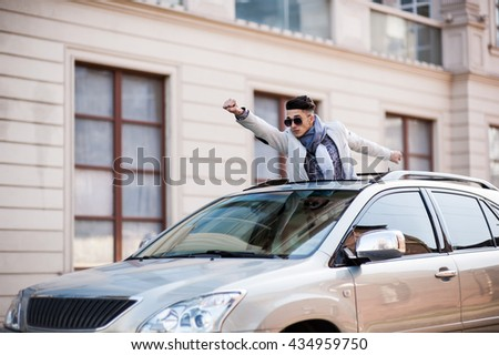 Free stylish man looking out from the roof of his own car