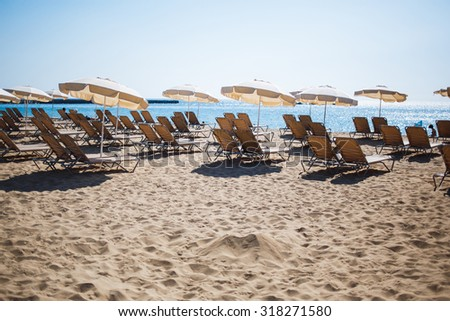 Free sun-beds and umbrellas on coastline near sea in summer day against blue sky background with copy space area for your text message or advertising content, relax and vacation holidays on the beach - stock photo