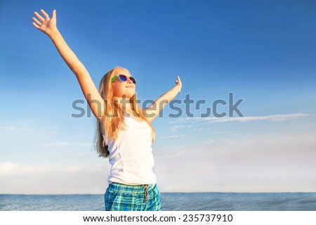 Free teenager (teen girl) relaxing, enjoying nature sunset on the sky background. Happy female model is is wearing sunglasses. Freedom, happiness and enjoyment concept. Summer. Outdoor. - stock photo