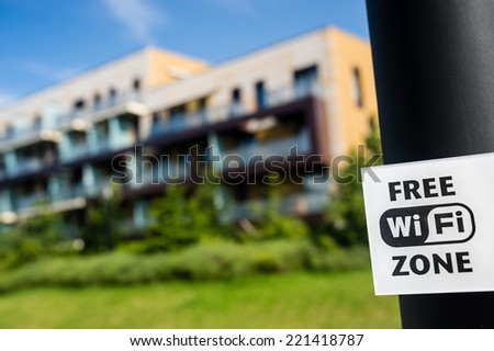 Free wi-fi zone sign in the public park in front of modern block of flats