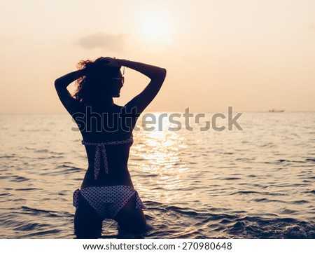 Free woman enjoying freedom feeling happy at beach at sunset. Beautiful serene relaxing woman in pure happiness and elated enjoyment with arms raised outstretched up. Latin Caucasian female model. - stock photo