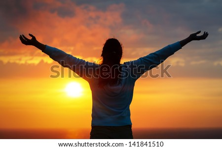 Free woman raising arms to golden sunset summer sky and ocean like praising. Freedom, success and hope concept. Girl relaxing and enjoying peace and serenity on beautiful nature. - stock photo