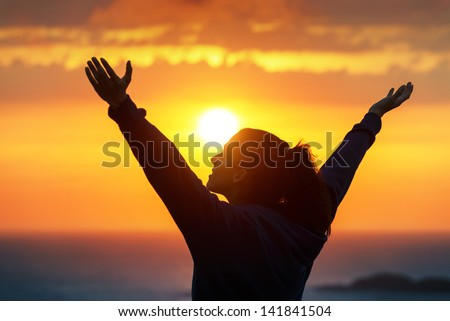 Free woman raising arms to golden sunset summer sky like praising. Freedom, success and hope concept. Girl relaxing and enjoying peace and serenity on beautiful nature. - stock photo